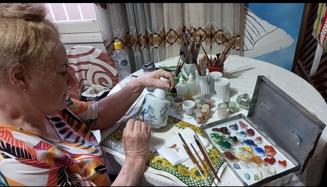 Artista plástica AnaMarB faz a pintura na peça